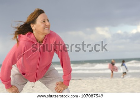 Portrait of confident, healthy and sporty fit attractive looking mature woman in pink sweater, at beach, isolated with storm clouds and ocean as background and copy space. - stock photo