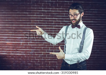 Portrait of confident hipster gesturing sideways against brick wall - stock photo