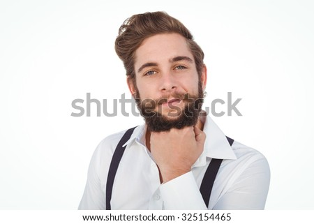 Portrait of confident hipster with hand on chin against white background