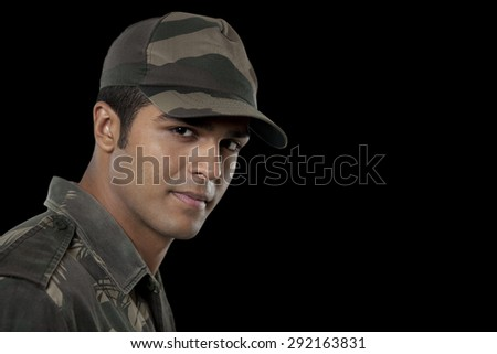 Portrait of confident Indian soldier over black background - stock photo