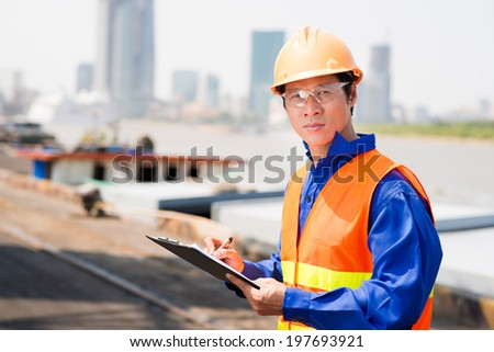 Portrait of confident inspector in the seaport - stock photo