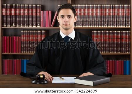 Portrait of confident judge against bookshelf in courtroom - stock photo