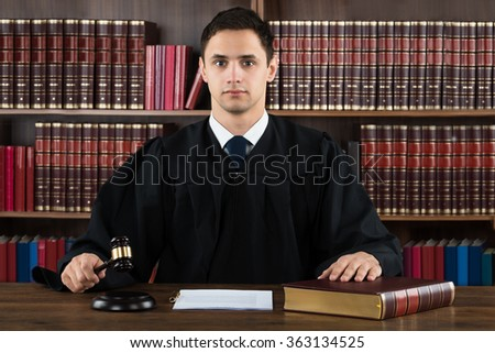 Portrait of confident judge hitting mallet at desk against bookshelf in courtroom - stock photo