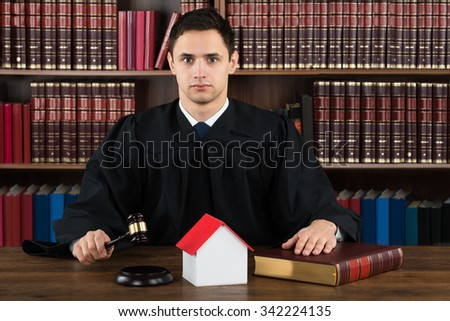 Portrait of confident judge with house model hitting gavel at desk against bookshelf in courtroom - stock photo