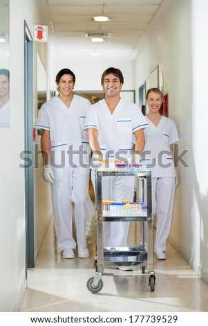 Portrait of confident lab technicians with medical cart walking in hospital corridor - stock photo