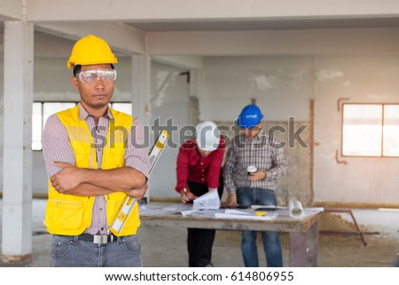 Portrait of confident Labor standing at front of engineer and foreman with safety helmet and level measurement on old buildings in their job site.