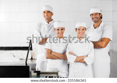 Portrait of confident male and female Baker's with arms crossed standing in bakery - stock photo