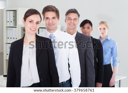 Portrait of confident male and female business colleagues standing together in office