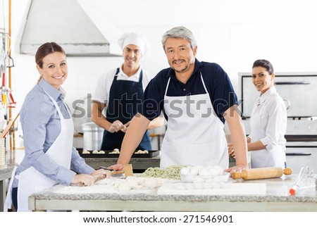 Portrait of confident male and female chefs preparing pasta at commercial kitchen - stock photo