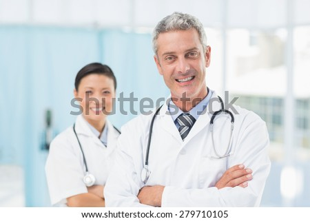 Portrait of confident male and female doctors at medical office - stock photo