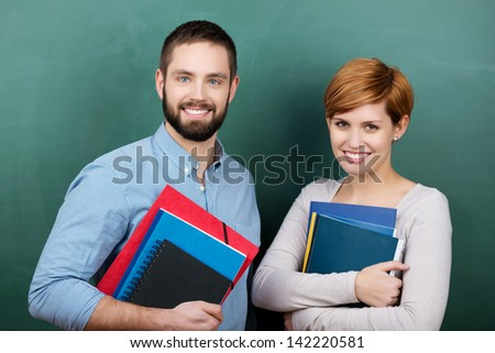 Portrait of confident male and female teachers holding books and files against chalkboard - stock photo