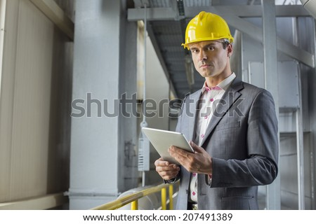 Portrait of confident male architect holding digital tablet in industry - stock photo