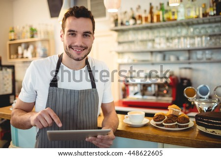 Portrait of confident male barista using digital tablet at counter in cafe - stock photo