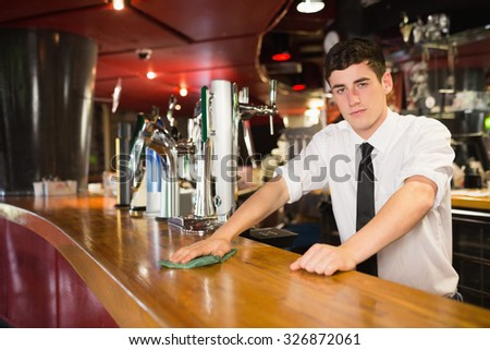 Portrait of confident male bartender cleaning bar counter - stock photo