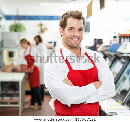 Portrait of confident male butcher standing arms crossed at store with colleagues working in background - stock photo