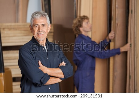 Portrait of confident male carpenter with arms crossed standing in workshop - stock photo