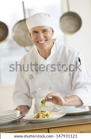 Portrait of confident male chef garnishing dish at counter in commercial kitchen - stock photo