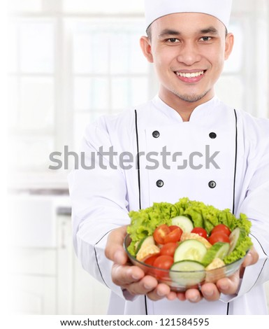 Portrait of confident male chef offering healthy food - stock photo