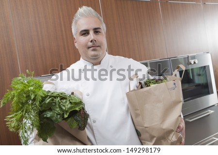 Portrait of confident male chef with two bags of fresh groceries in commercial kitchen - stock photo