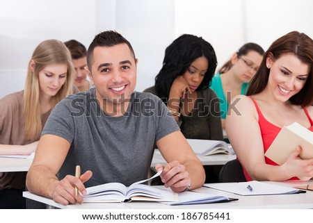 Portrait of confident male college student sitting at desk with classmates in background - stock photo