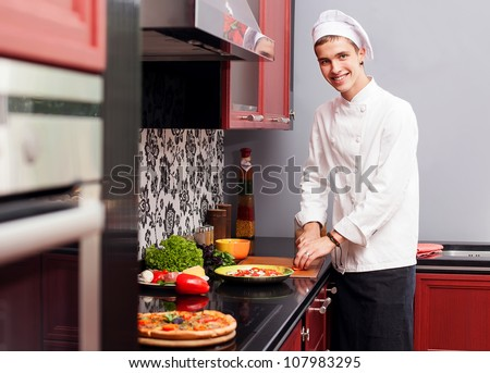 Portrait of confident male cook in modern restaurant kitchen smiling - stock photo