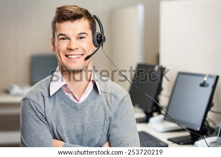 Portrait of confident male customer service representative with headset in call center - stock photo