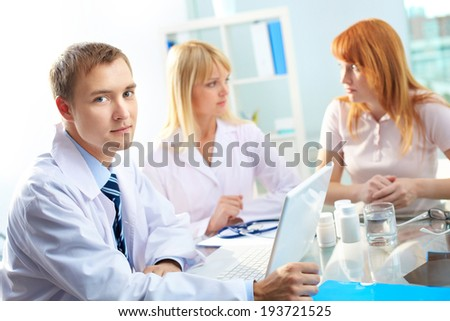 Portrait of confident male doctor looking at camera in working environment - stock photo