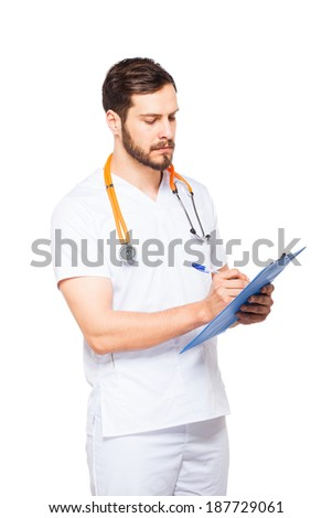 Portrait of confident male doctor with stethoscope writing on clipboard, isolated on white background - stock photo
