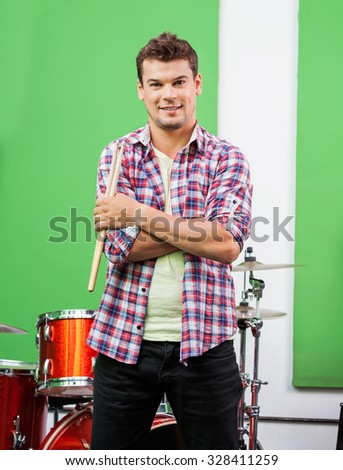 Portrait of confident male drummer holding sticks while standing arms crossed in recording studio - stock photo