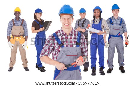 Portrait of confident male engineer holding tool with team against white background - stock photo