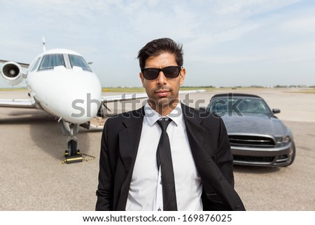 Portrait of confident male entrepreneur in front of car and private jet - stock photo
