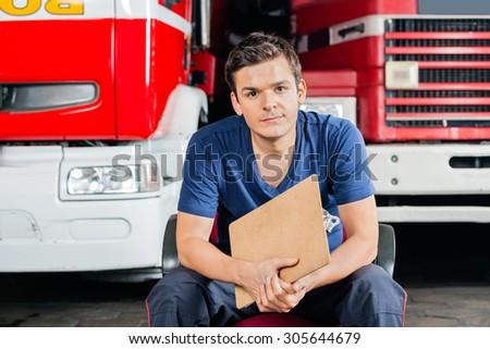 Portrait of confident male firefighter holding clipboard while sitting against firetrucks at station - stock photo
