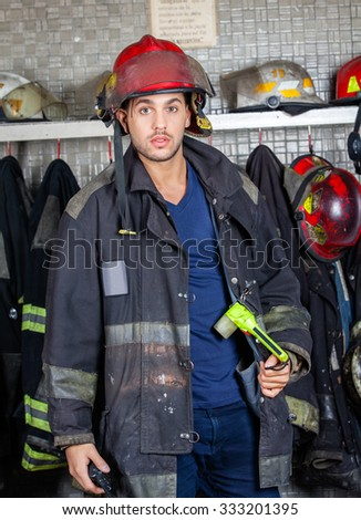 Portrait of confident male firefighter in uniform standing at fire station