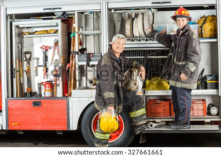 Portrait of confident male firefighters standing on truck at fire station - stock photo