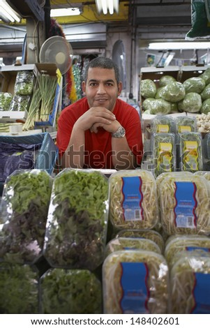 Portrait of confident male grocery store owner leaning at counter - stock photo