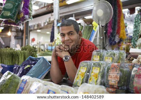 Portrait of confident male grocery store owner smiling while leaning on counter - stock photo