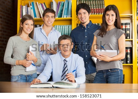 Portrait of confident male librarian with students in college library