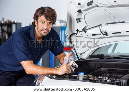 Portrait of confident male mechanic leaning on car with open hood at garage