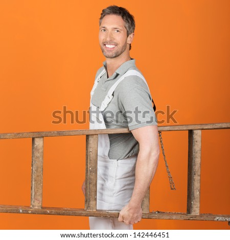 Portrait of confident male painter carrying wooden ladder against orange painted wall - stock photo