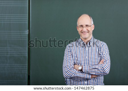 Portrait of confident male professor with arms crossed standing against chalkboard in classroom - stock photo