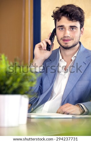 Portrait of confident male receptionist using cordless phone at counter in office - stock photo