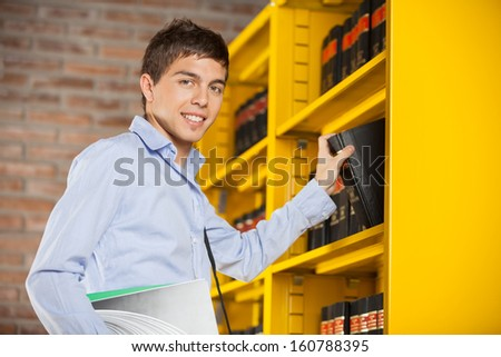 Portrait of confident male student taking book from shelf in library