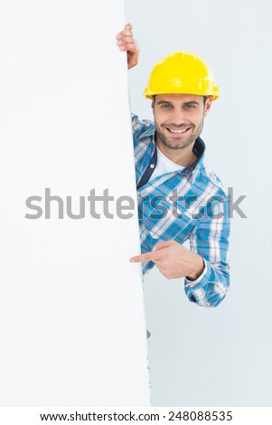 Portrait of confident male technicial pointing at blank billboard on white background