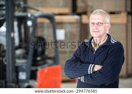 Portrait of confident male worker standing arms crossed at distribution warehouse - stock photo