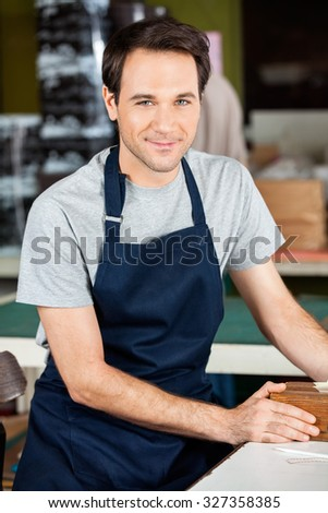 Portrait of confident male worker wearing blue apron in paper factory
