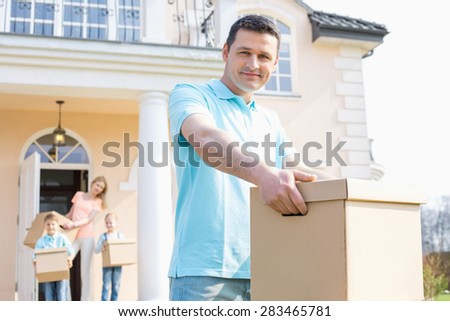 Portrait of confident man carrying cardboard box while moving house with family in background - stock photo
