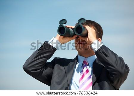 Portrait of confident man in suit observing through binoculars somewhere outside - stock photo