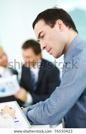 Portrait of confident man looking at document in his partner hand - stock photo