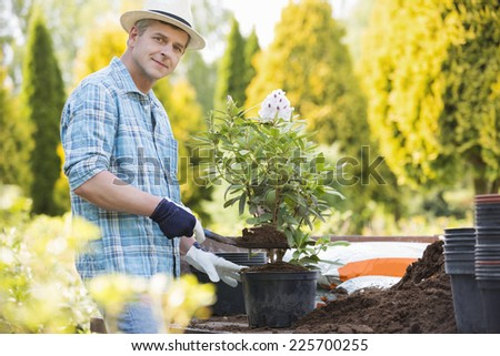 Portrait of confident man planting pot at garden - stock photo