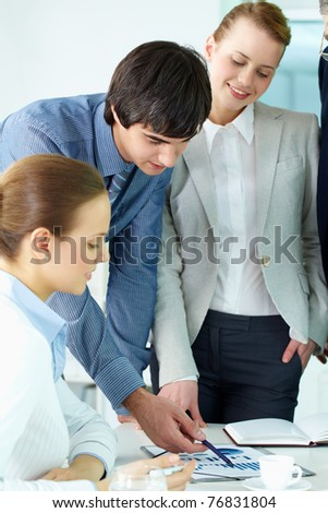 Portrait of confident man pointing at document surrounded by females in office